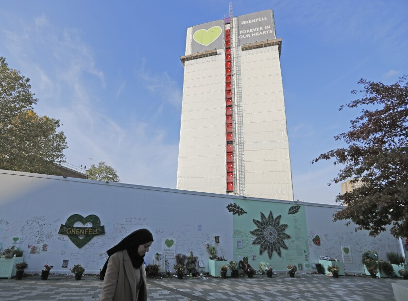 A woman passes a construction wall with written messages near Grenfell Tower in London, Wednesday, Oct. 30, 2019. A report released Wednesday on the deadly apartment block fire in London has condemned the London Fire Brigade and concluded that fewer people would have died if the building were evacuated more quickly. (AP Photo/Frank Augstein)