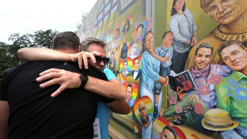Artist Yuriy Karabash hugs a family member of a victim at the Pulse nightclub, Monday, June 12, 2017