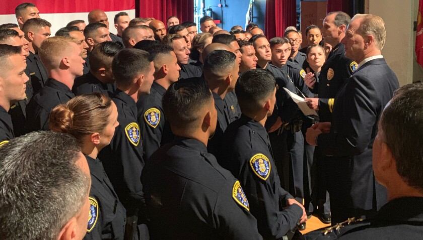 At a graduation ceremony at MCAS Miramar on Thursday, a group of new police academy graduates listen to San Diego police Chief David Nisleit (near the right, holding a piece of paper). Standing on Nisleit's left is San Diego Mayor Kevin Faulconer. Thursday's graduating class of 58 newly sworn officers marked the police department's largest graduating class of police recruits in 25 years.