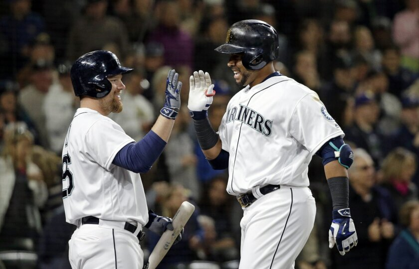 Seattle Mariners' Adam Lind, left, greets Nelson Cruz after Cruz's home run against the Oakland Athletics during the seventh inning of a baseball game Wednesday, May 25, 2016, in Seattle. (AP Photo/Elaine Thompson)