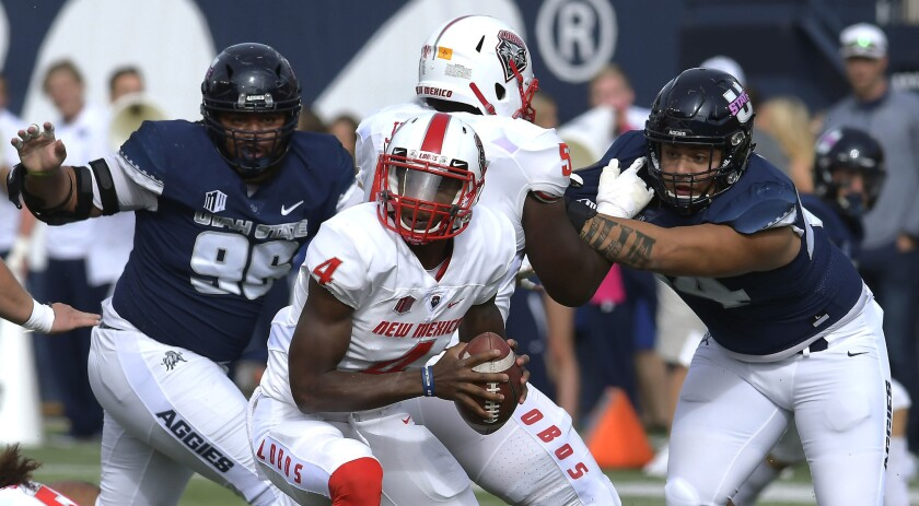 New Mexico quarterback Sheriron Jones (4) runs with the ball as Utah State's Christopher Unga (96) a