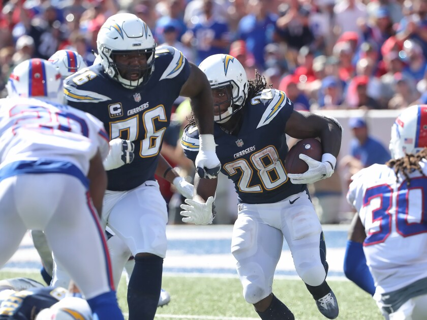 Chargers tackle Russell Okung (76) leads the way for running back Melvin Gordon during a game last season.