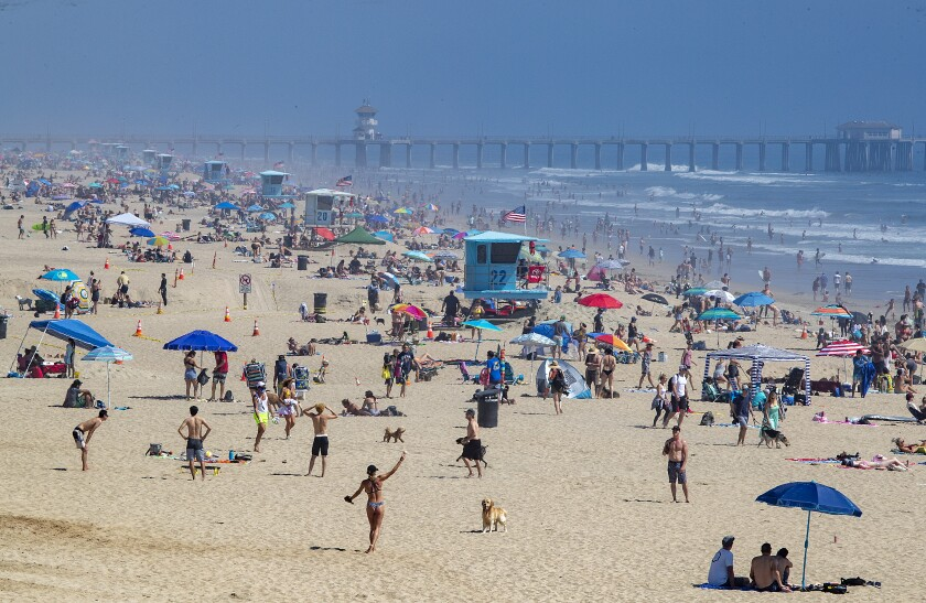 HUNTINGTON BEACH, CA -- SATURDAY, APRIL 25, 2020: Thousands of beach-goers enjoy a warm, sunny day at the beach amid state-mandated stay-at-home and social distancing mandate to stave off the coronavirus pandemic in Huntington Beach, CA, on April 25, 2020. (Allen J. Schaben / Los Angeles Times)