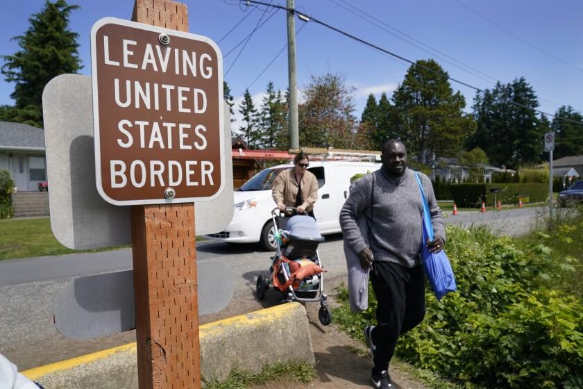 Los residentes canadienses Philip Owira (derecha) y Katherine Nichol cruzan la frontera de Canadá
