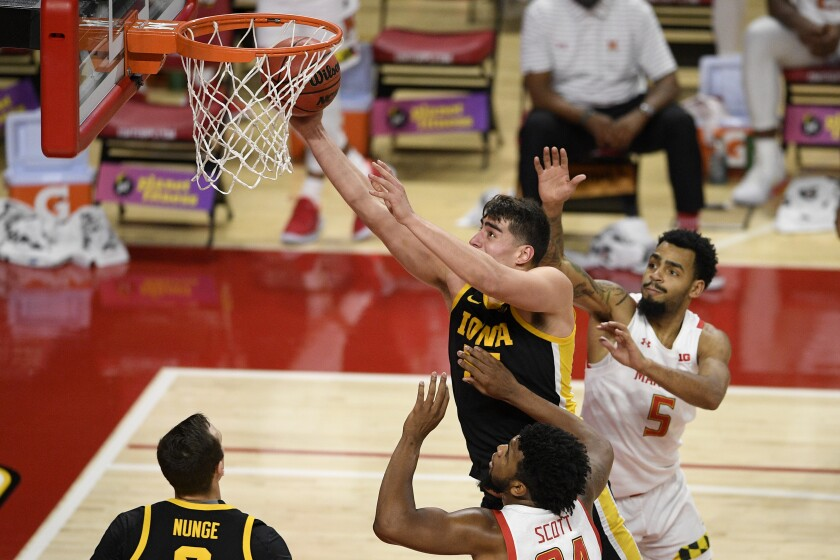 Iowa center Luka Garza, top left, goes to the basket between Maryland forward Donta Scott (24) and guard Eric Ayala (5) during the first half of an NCAA college basketball game, Thursday, Jan. 7, 2021, in College Park, Md. (AP Photo/Nick Wass)