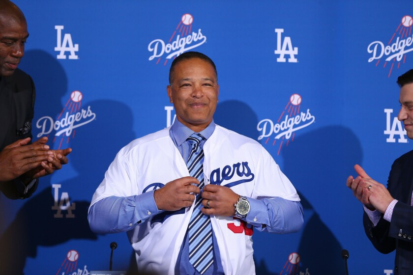 New manager Dave Roberts puts on a Dodgers jersey at the news conference Tuesday.
