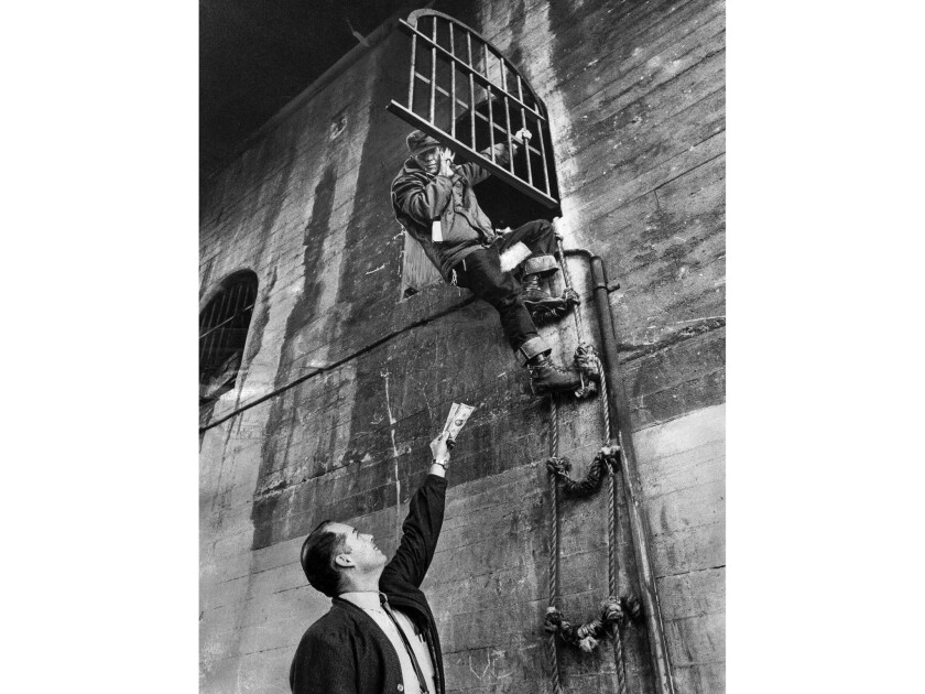 Dec. 23, 1969: Preston Tingle comes down rope ladder from his pad under 7th Street Bridge to accept his $25 reward from freight terminal manager Jim Hammett.