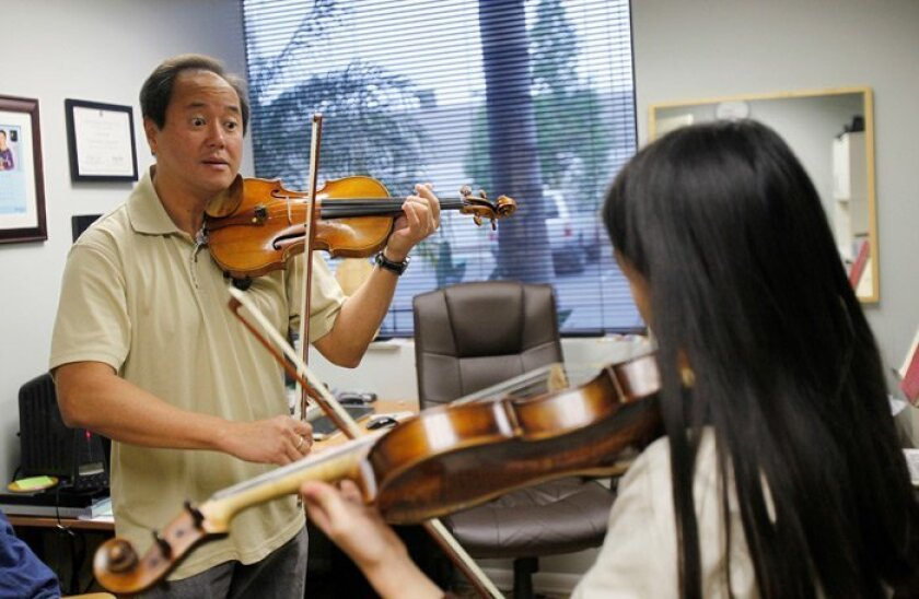 San Diego Symphony violinist Hernan Constantino taught a private lesson to Jenny Chen, 11, of Black Mountain Middle School. Educational outreach is an essential part of the job for members of the symphony.