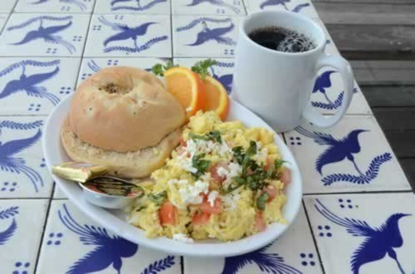The Greek Eggs are served with oranges and a bagel from Busy Bee's. A cup of coffee rounds out the full breakfast.