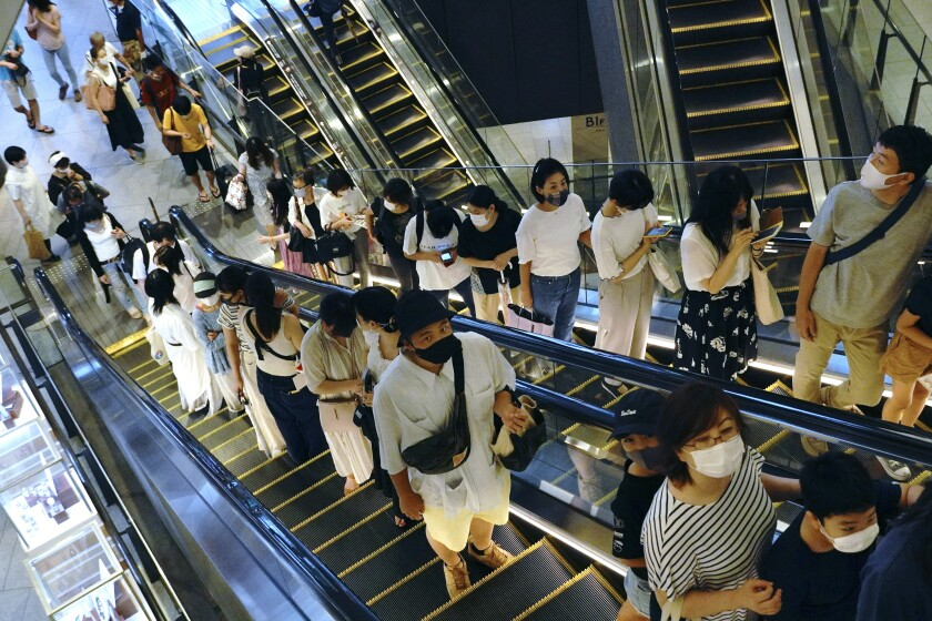 People take elevators at a shopping building in Tokyo on Aug. 24, 2020. Japanese manufacturers' sentiments improved for the first time in three years, a quarterly Bank of Japan survey showed Thursday, Oct. 1, 2020, as the nation grappled with stagnation worsened by the coronavirus pandemic. (AP Photo/Eugene Hoshiko)