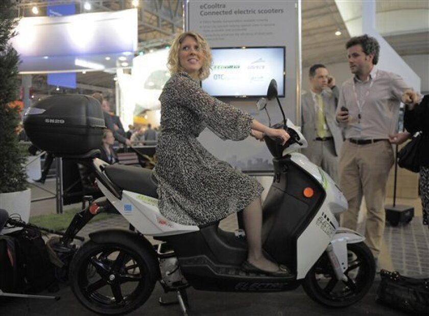 In this Tuesday, Feb. 26, 2013, photo, a woman sits on an eCooltra Connected electric scooters at the Mobile World Congress, the world's largest mobile phone trade show, in Barcelona, Spain. The first wave of the wireless revolution was getting people to talk to each other through cellphones. The s