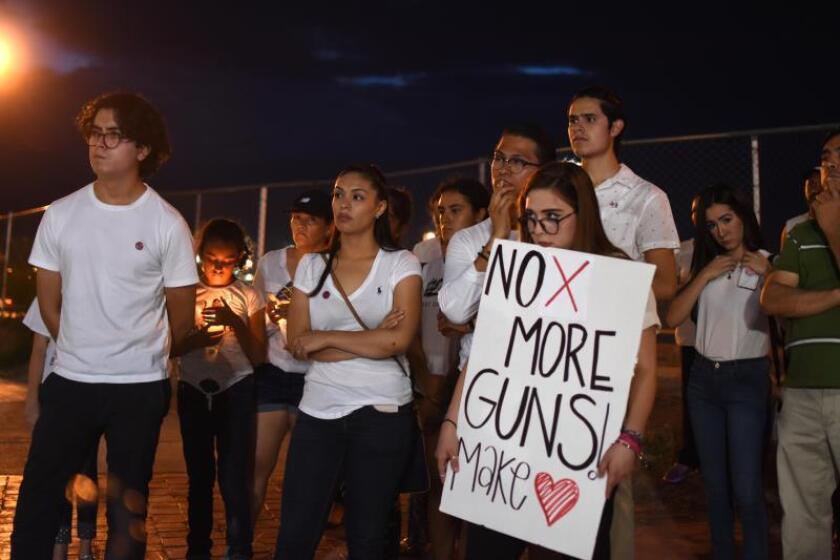 Decenas de personas oran en la línea fronteriza de Ciudad Juárez (México), tras el tiroteo en un centro comercial de El Paso, Texas (EEUU), que arrebató la vida a una veintena de personas.