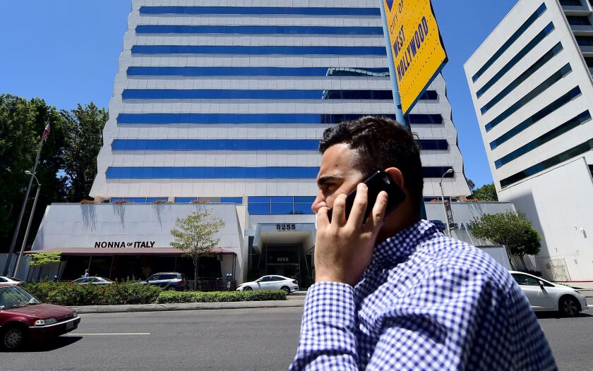 A pedestrian speaks on his cellphone while walking on Sunset Boulevard in West Hollywood on July 20.