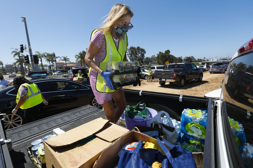 Caroline Thiss-Aird loads the back of her truck of donated items during donation food drive in Carlsbad on Saturday morning. The donated food and household item will be given to local farm workers at three farms in San Diego County.