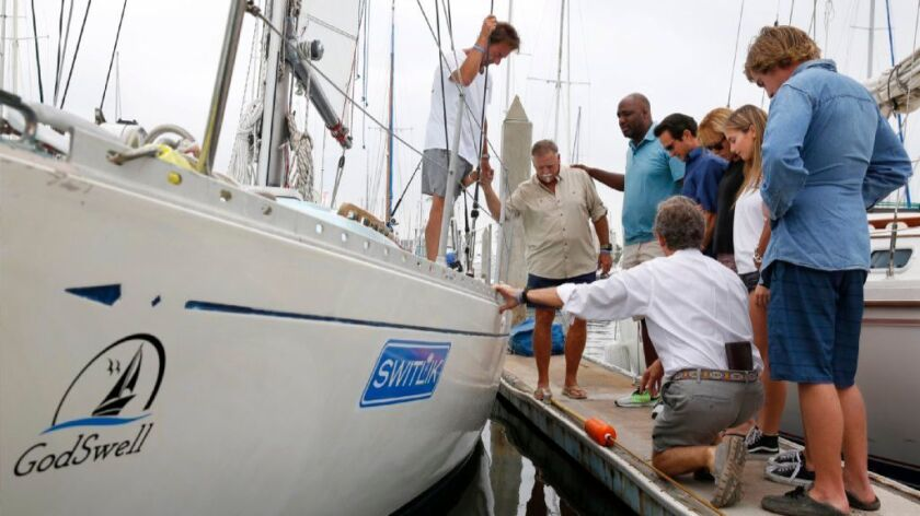 John Silverwood prays with friends and family before setting off on a solo sailing trip from San Die