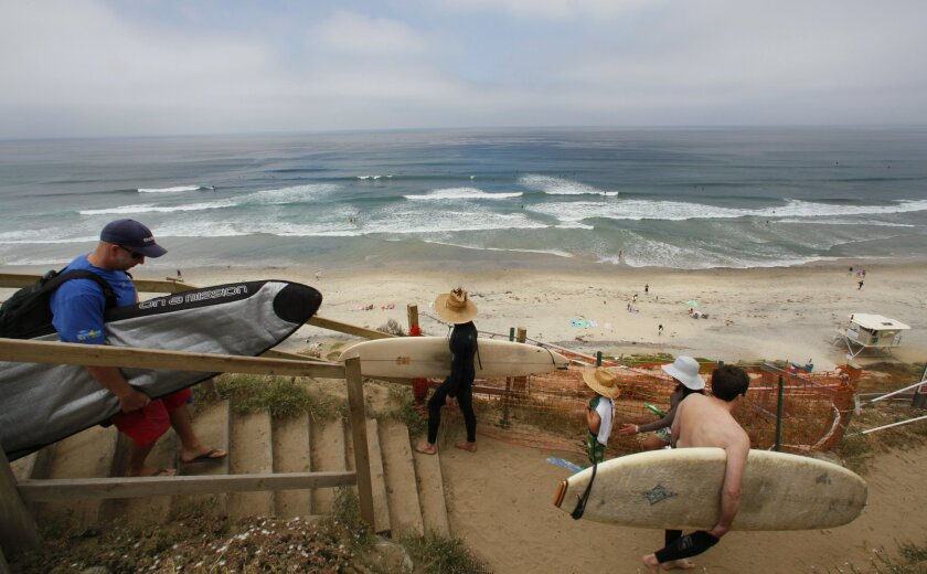 """At Beacon Beach in Encinitas, surfers make their way on the dirt trail to the beach. In 2001, the city sought a state grant to build a new trail and a """"toehold bluff stabilization device,"""" a partially buried sea wall. The state initially awarded the grant but withdrew it late last year. Nelvin C. C"""