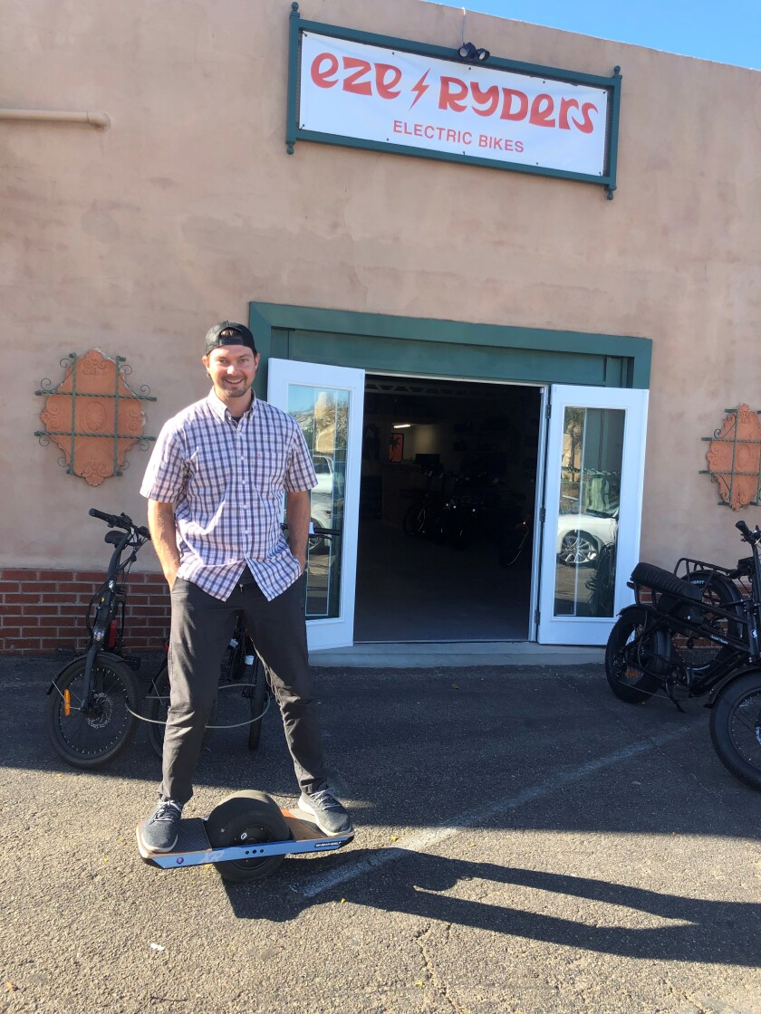 Devin Raymond rolls up outside his new electric bicycle shop, EZE Ryders in Point Loma.