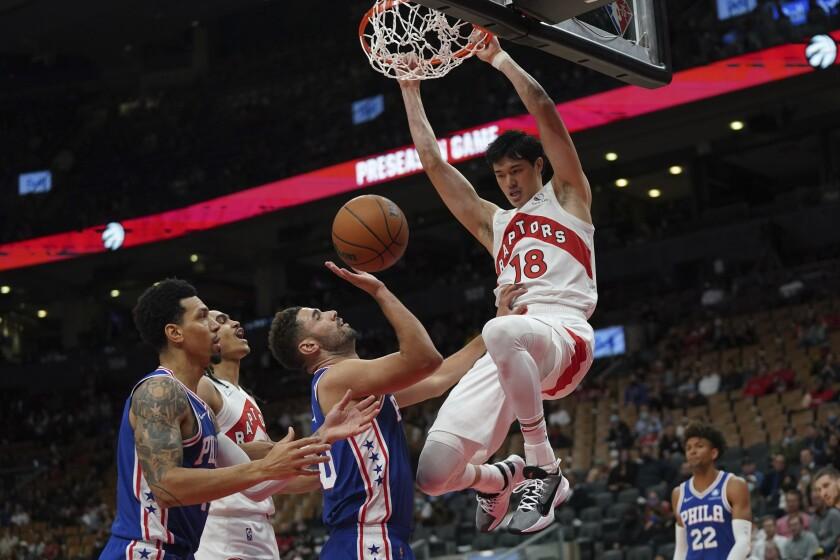 Toronto Raptors forward Yuta Watanabe (18) slam-dunks over Philadelphia 76ers' Georges Niang, center, during first-half preseason NBA basketball action in Toronto, Monday, Oct. 4, 2021. (Nathan Denette/The Canadian Press via AP)