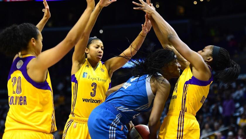The Sparks' Nneka Ogwumike, left, Candace Parker and Kristi Toliver surround Minnesota's Sylvia Fowles on Sunday.