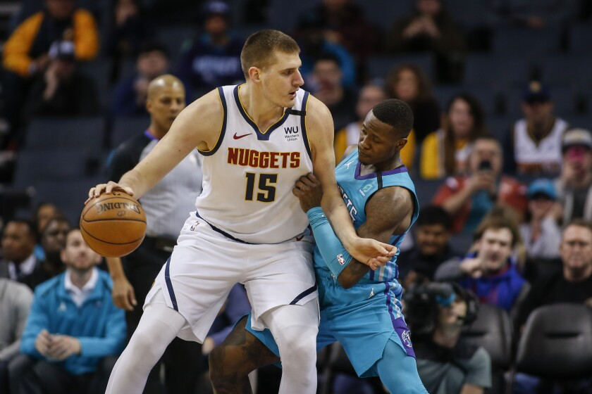 Denver Nuggets center Nikola Jokic, left, drives into Charlotte Hornets guard Terry Rozier.
