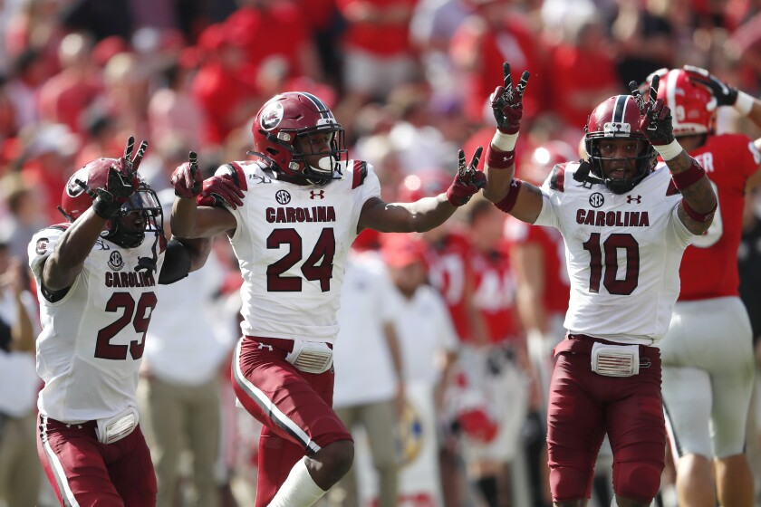 South Carolina defensive backs Israel Mukuamu (24) celebrates with J.T. Ibe (29) and R.J. Roderick (10) after intercepting a pass in the second half of an NCAA college football game against Georgia, Saturday, Oct. 12, 2019, in Athens, Ga. South Carolina won 20-17 in double overtime. (AP Photo/John Bazemore)