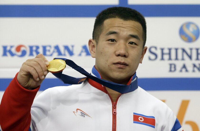 FILE - In this Sept. 23, 2014, file photo, North Korea's gold medalist of the men's 56kg weightlifting Om Yun Chol poses with his gold medal during a press conference at the 17th Asian Games in Incheon, South Korea. Om Yun-chol is the front-runner to win another gold in men's 56-kilogram category, the lightest weight class, at the Rio Olympics. (AP Photo/Lee Jin-man, File)