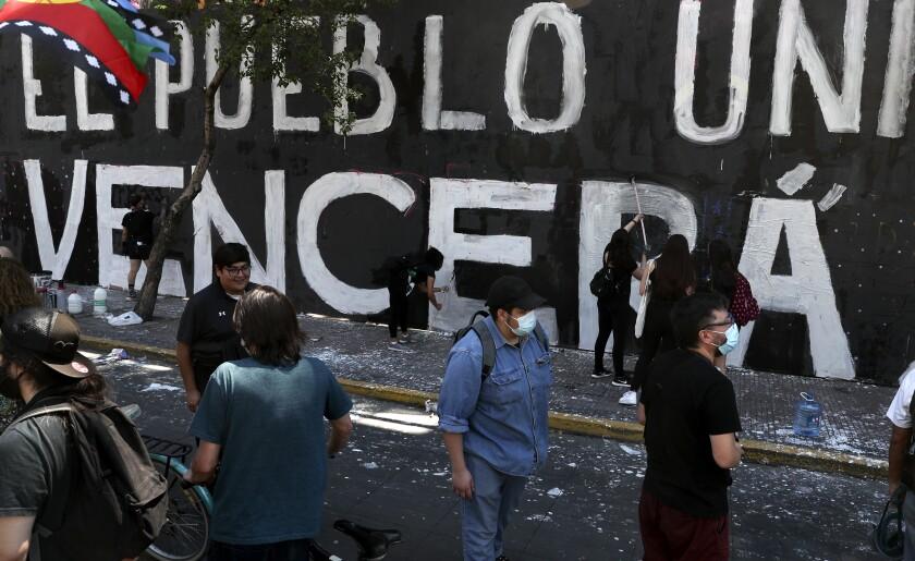 Manifestantes pintan una pared mientras conmemoran el aniversario del estallido social de 2019 en protesta a un incremento en las tarifas del metro en Santiago de Chile el domingo 28 de octubre de 2020. (AP Foto/Esteban Felix)
