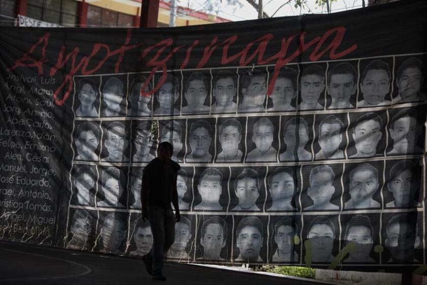 Un joven mexicano camina frente a un cartel con imágenes de los 43 estudiantes desaparecidos en Ayotzinapa. EFE/Archivo