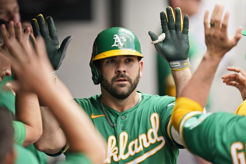 Oakland Athletics' Mitch Moreland is congratulated by teammates after hitting a solo home run in the fifth inning of a baseball game against the Cleveland Indians, Thursday, Aug. 12, 2021, in Cleveland. (AP Photo/Tony Dejak)