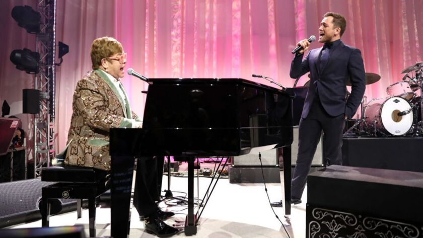 "Elton John and Taron Egerton perform at the singer's annual Oscar party in Los Angeles in February. The actor will play the musician in the upcoming ""Rocketman."""