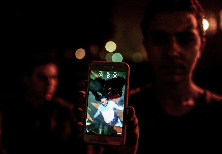 EDS NOTE: GRAPHIC CONTENT - In this Thursday, Feb. 18, 2016 photo, a man shows a photo he took on his mobile phone of a driver who was killed by a police officer, in a dispute in Cairo, Egypt. Egypt's Interior Ministry media office said in a statement that the killing followed an argument over the