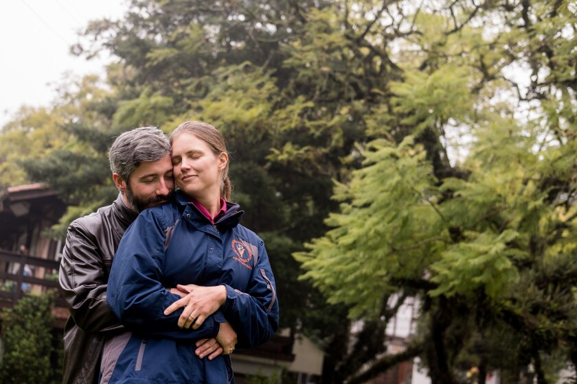 Falko König embraces Kathleen Morriss as they walk in a scenic square in a city in southern Brazil.