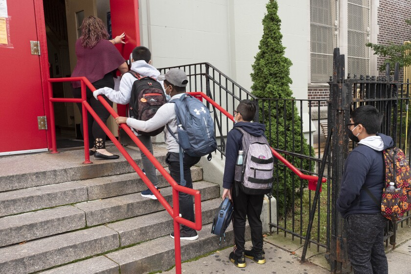 Elementary students go into a Brooklyn, New York school Tuesday