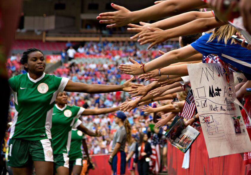 Nigeria forward Ini-Abasi Umotong greets fans before a match against the United States during the 2015 Women's World Cup.