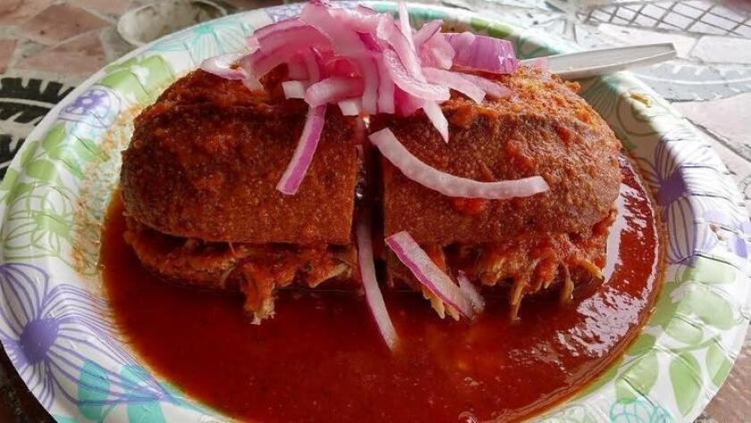 The classic torta ahogada made with birote bread, lean roasrkted pork, chile de arbol sauce and pickled onions. (Amy T. Granite)