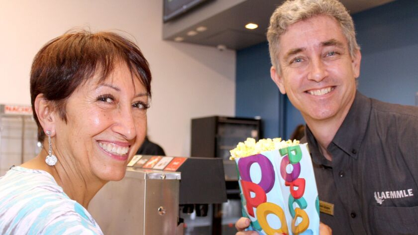 Gloria Salas couldn't be without her popcorn at Laemmle Glendale's grand opening. Kevin Gallagher, Laemmle director of operations obliges.