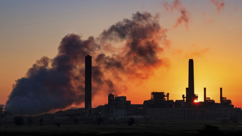 In this July 27, 2018 photo, the Dave Johnson coal-fired power plant is silhouetted against the morn