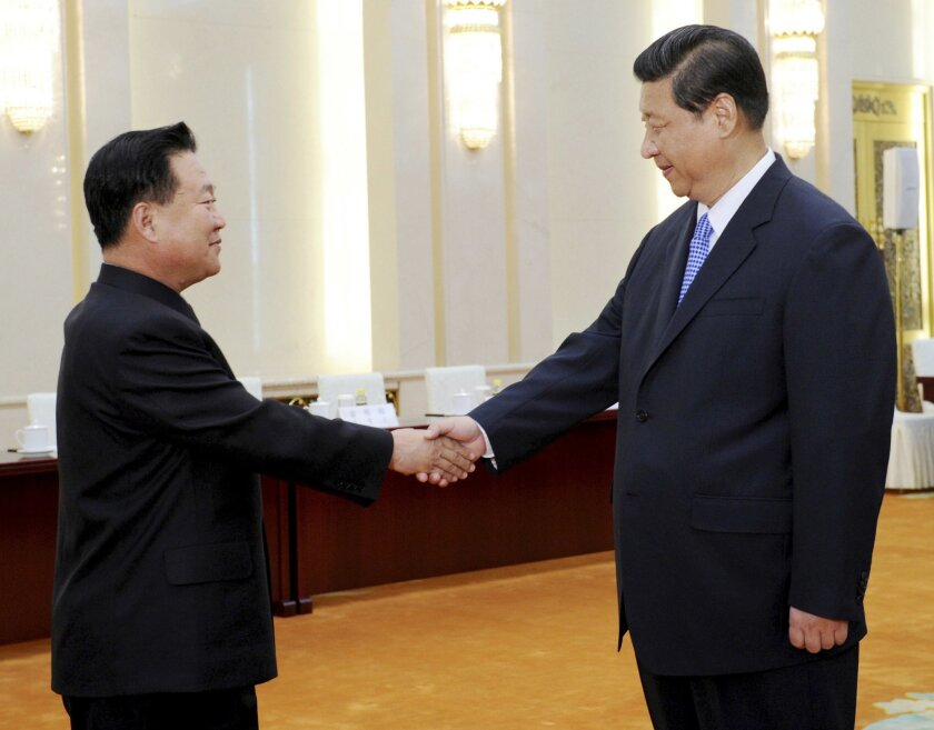 FILE - In this May 24, 2013, file photo released by China's Xinhua News Agency, North Korean Vice Marshal Choe Ryong Hae, left, is greeted by Chinese President Xi Jinping in Beijing when the top North Korean envoy delivered a letter from leader Kim Jong Un to Xi and told him Pyongyang would take steps to rejoin stalled six-nation nuclear disarmament talks. If North Korea launches a rocket into space or conducts a nuclear test in the coming weeks, marking the 70th anniversary of the founding of its ruling Workers Party on Oct. 10, 2015, as observers suspect it may, China is certain to respond angrily, and perhaps with an unprecedented level of economic punishment. (Rao Aimin/Xinhua News via AP) NO SALES