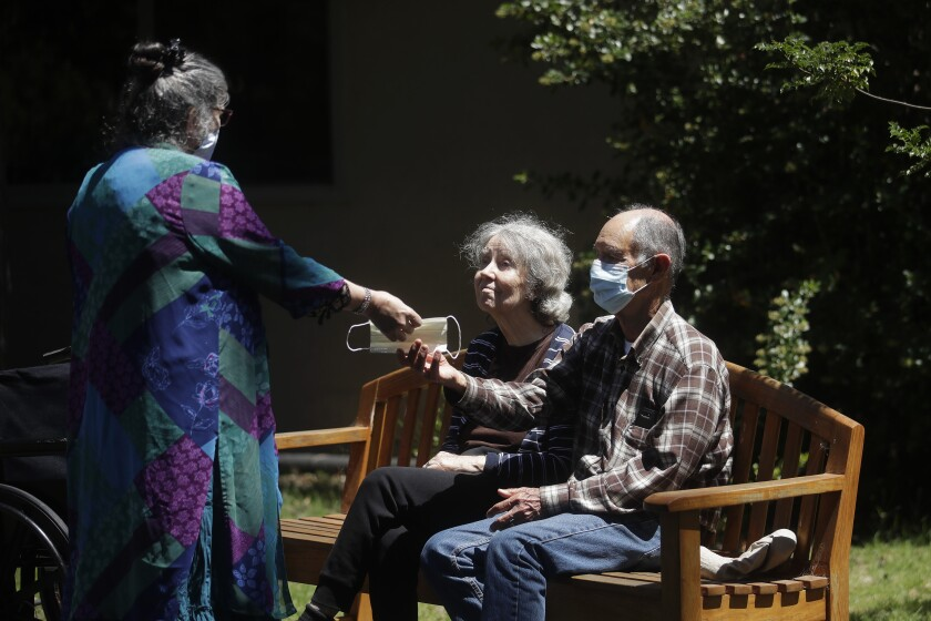 A nursing home director hands a mask to an elderly couple sitting on a bench during an outdoor visit at the facility