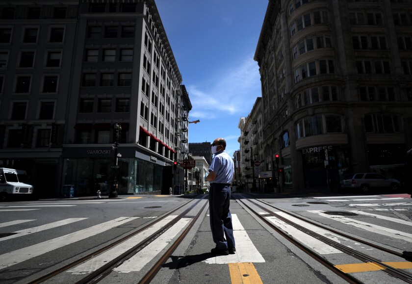 A U.S. Postal Service letter carrier stands in the middle of Powell Street in San Francisco. San Francisco, San Mateo and Marin plan to incrementally ease their social-distancing restrictions starting Monday.