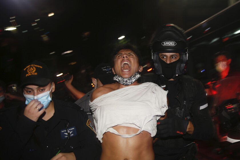 Israeli police officers arrest an Israeli protester during a demonstration against lockdown measures that they believe are aimed at curbing protests against Prime Minister Benjamin Netanyahu, in Tel Aviv, Israel, Saturday, Oct. 3, 2020. (AP Photo/Ariel Schalit)