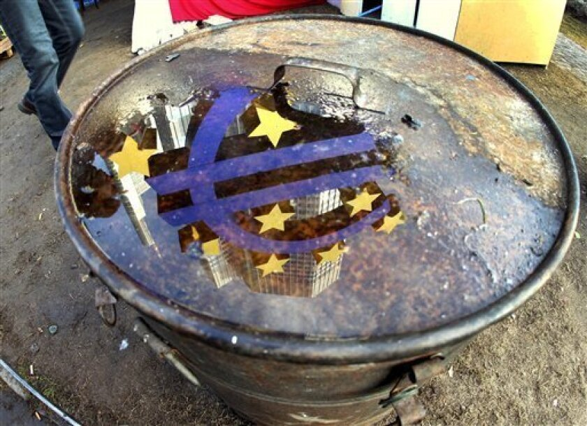 The Euro sculpture is reflected in a puddle on the lid of a bin that stands in the Frankfurt Occupy camp at the European Central Bank in Frankfurt, Germany, Wednesday, Nov.30, 2011.(AP Photo/Michael Probst)