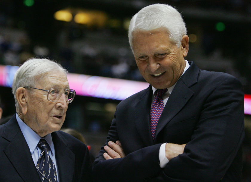 Former UCLA coach John Wooden, left, speaks with Arizona coach Lute Olson after a game in 2004.