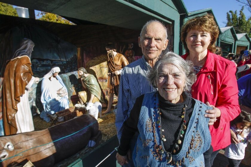 Artist Barbara Jacobson, right, and Betty and Woody Whitlock, who worked together to restore the figurines for the Community Christmas Center's Nativity display for December Nights at Balboa Park in San Diego on Saturday.