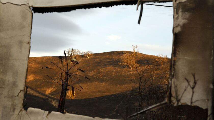 The charred hills of Calabasas are seen through a burned-out structure after the Woolsey fire.