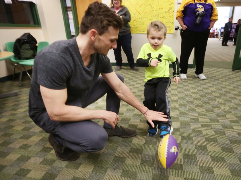 Max Birdwell, 4, kicks a football from the hold of Minnesota Vikings kicker Blair Walsh during the player's visit to Northpoint Elementary on Thursday.