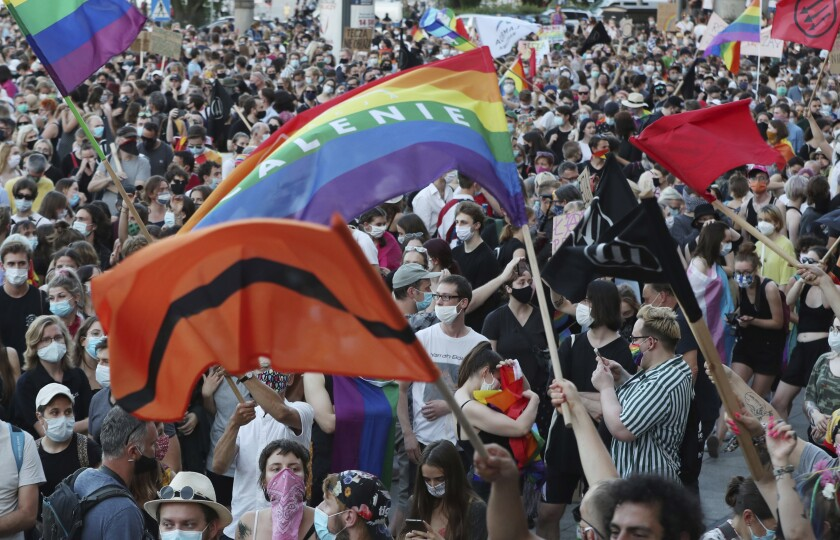 A masked crowd waves rainbow flags at a rally