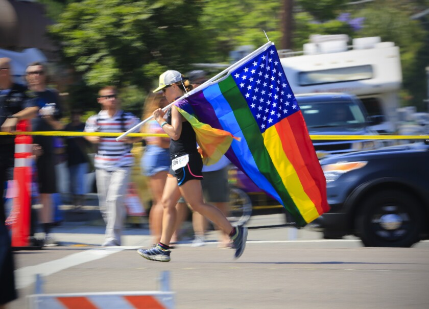 A runner in the San Diego LGBT Pride 5K carries an American flag along the race route through Hillcrest fashioned with gay pride colors.