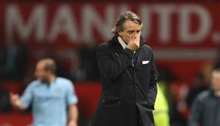 Manchester City's manager Roberto Mancini walks from the pitch after his team's 2-1 win over Manchester United in their English Premier League soccer match at Old Trafford Stadium, Manchester, England, Monday, April 8, 2013. (AP Photo/Jon Super)