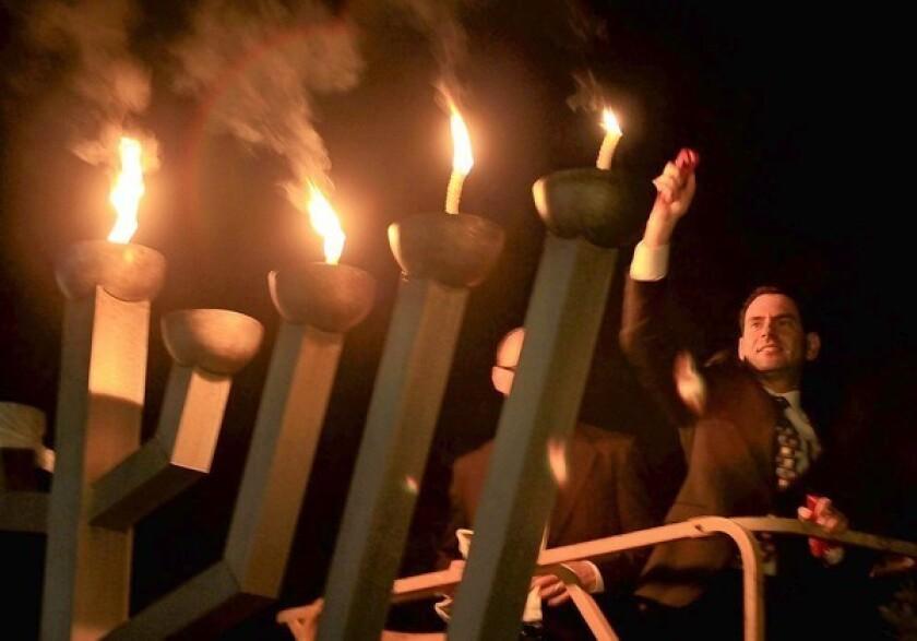 Giant menorah lit on temple lawn